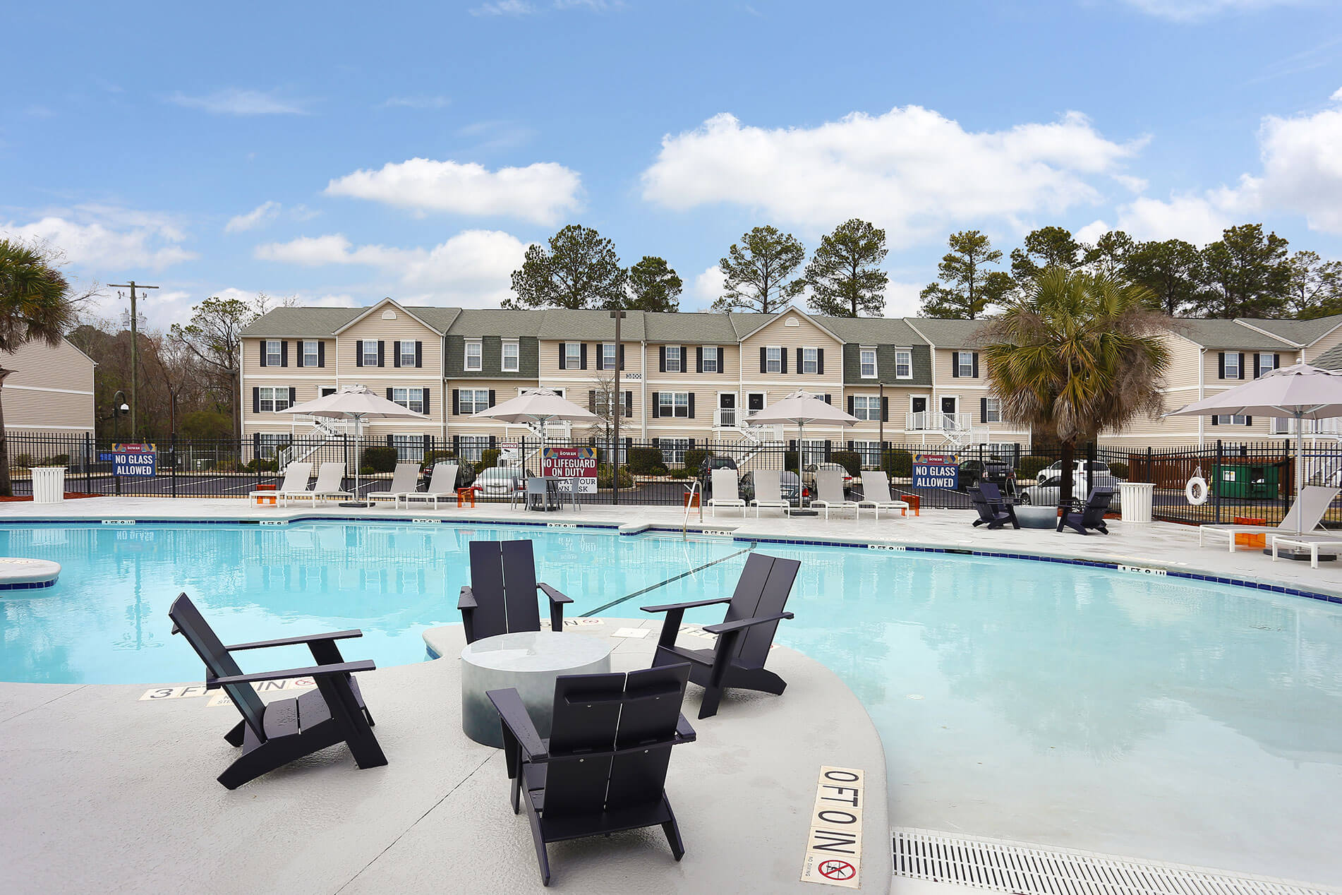 Outdoor Pool With Buildings in the Background at The Rowan Apartments