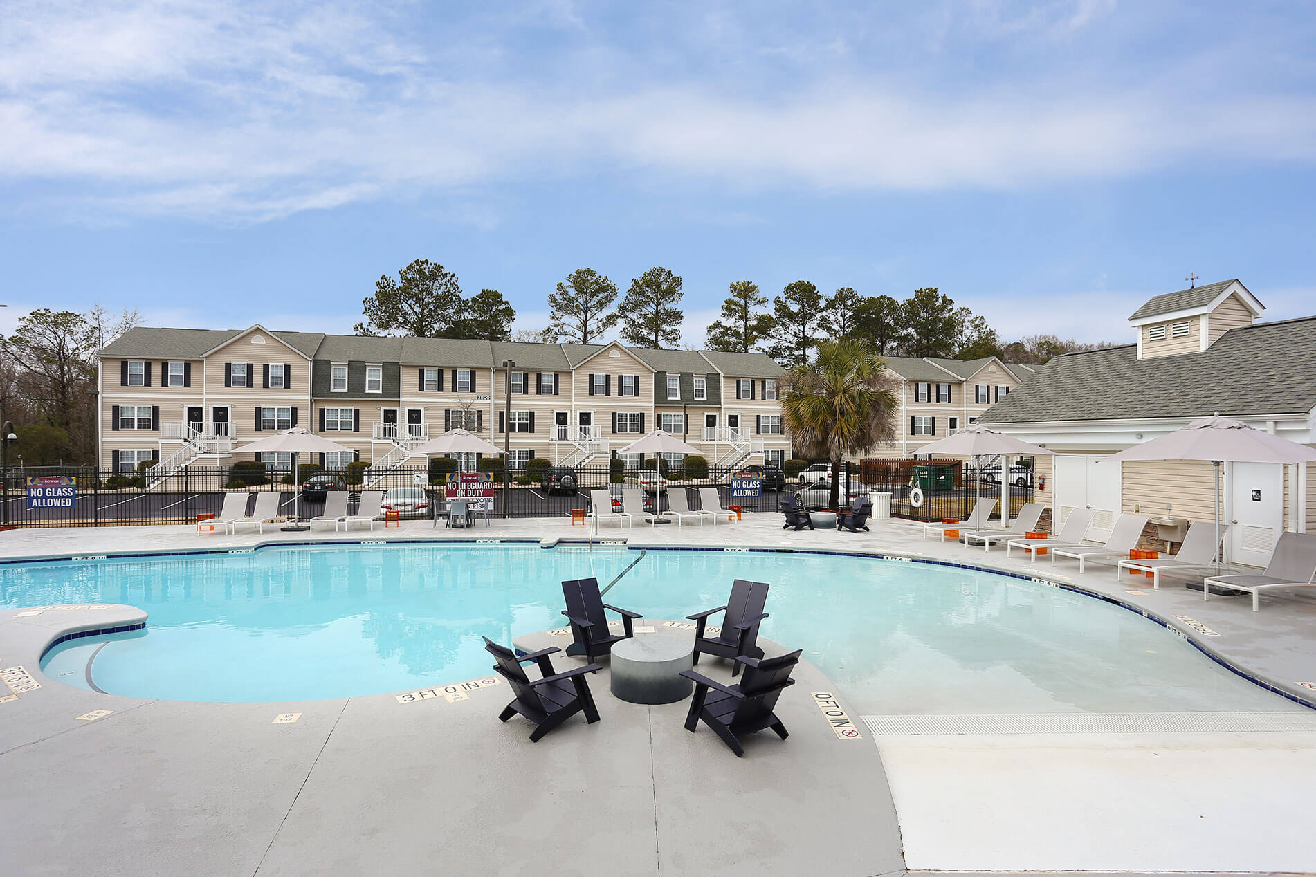 Outdoor Pool With a Table and Chairs at The Rowan Apartments